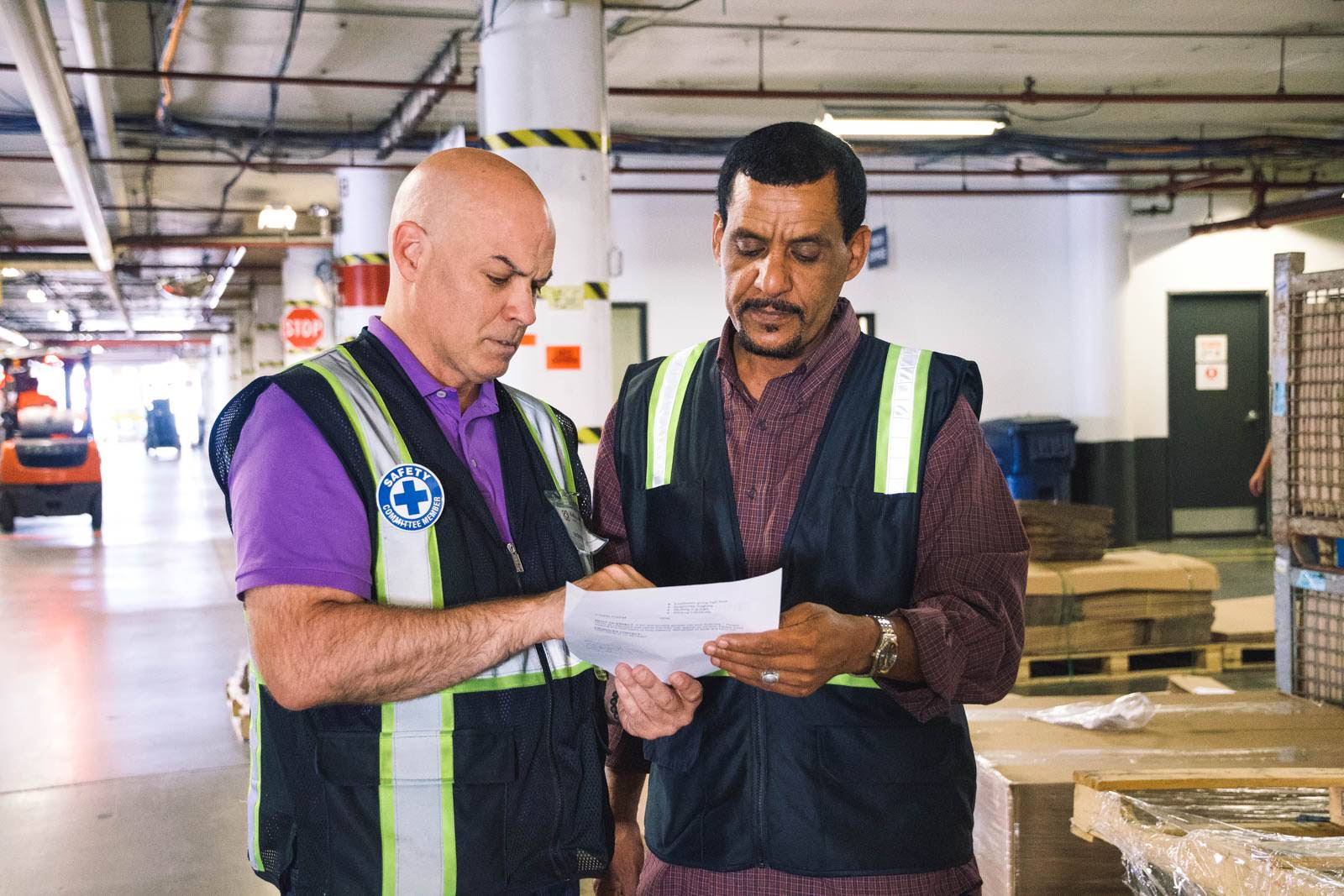 Two warehouse employees review an order form together