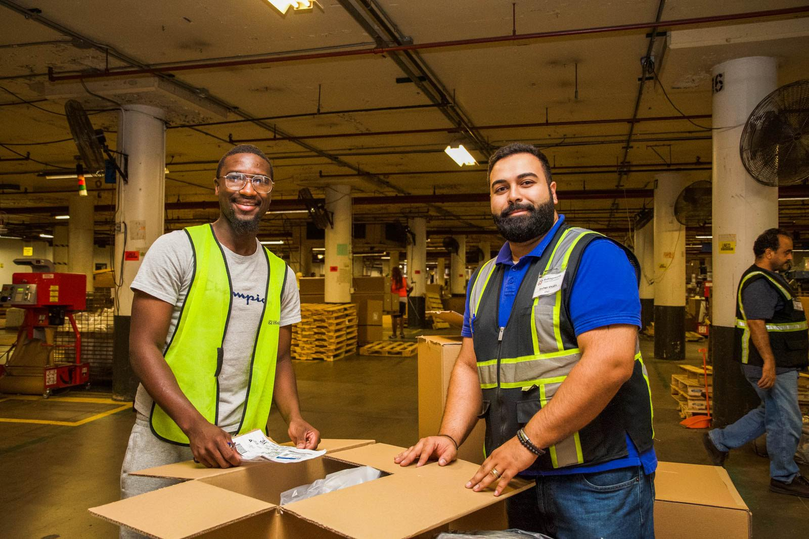 Two smiling warehouse employees unbox a package