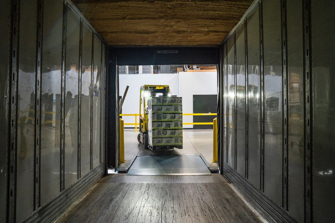 forklift truck loading a cargo container